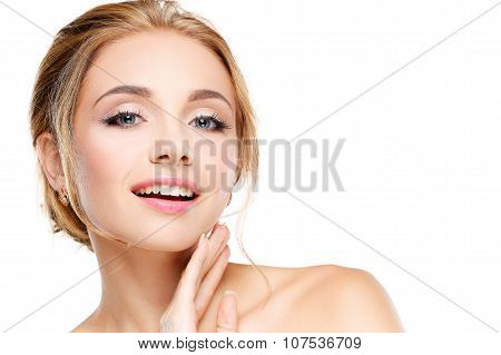 Studio shot of a beautiful young woman with perfect skin against a gray background.