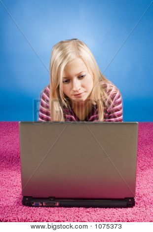 Young Blonde Woman Lying On The Pink Carpet With Laptop