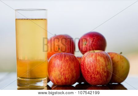 apple juice with apples on a wooden table, outdoor