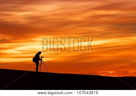 Nature photographer taking photos in the desert at sunrise