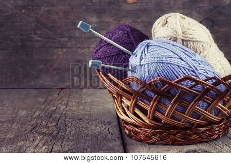 Skeins Colored Yarn And Knitting Needles In A Basket