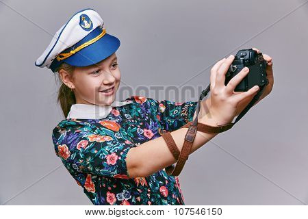 Girl in captain cap makes self camera.