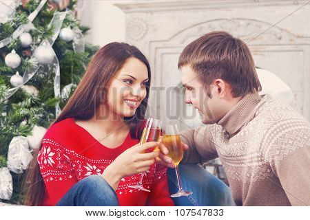Young Happy Couple Drinking Champagne By The Cristmas Tree