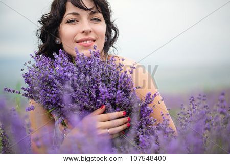 Young woman harvesting lavender flowers