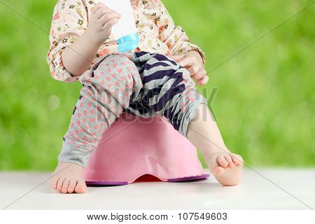 Children's Legs Hanging Down From A Chamber-pot On A Green  Background