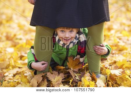 Boy In Park Looking Through Mother's Skirt