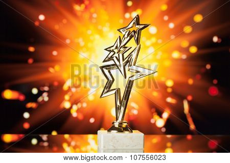 gold stars trophy against shiny sparks background