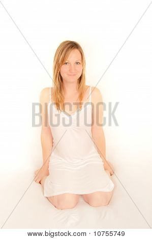 Cute Young Woman Sitting On Bed In Her Nightdress