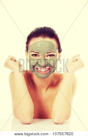 Beautifu toplessl woman with facial mask with hands on table.