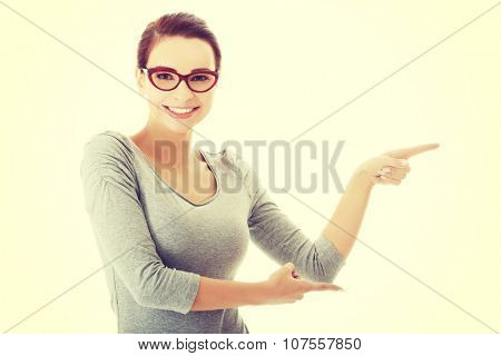 Beautiful casual woman in eyeglasses pointing aside