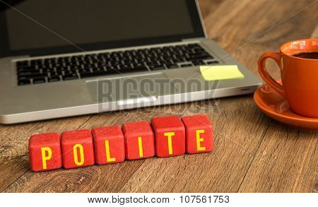 Polite written on a wooden cube in front of a laptop