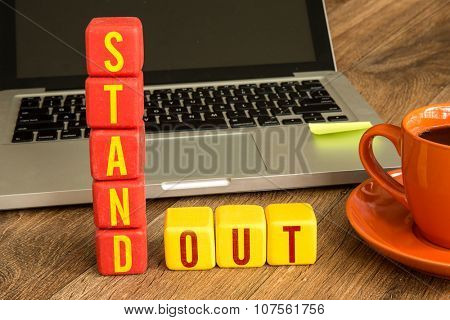 Stand Out written on a wooden cube in front of a laptop