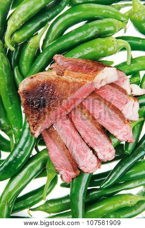 meaty food : roast meat steak sliced over green hot chili peppers on a white background