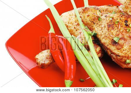 meat food : grilled quarter chicken garnished with green sprouts and red peppers on red plate isolated over white background