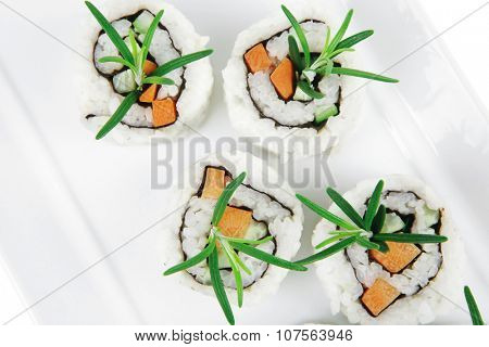 Japanese Cuisine - California Roll made of Fresh raw Salmon, Cream Cheese and Avocado inside. Served with wasabi and ginger . on long white plate isolated over white background