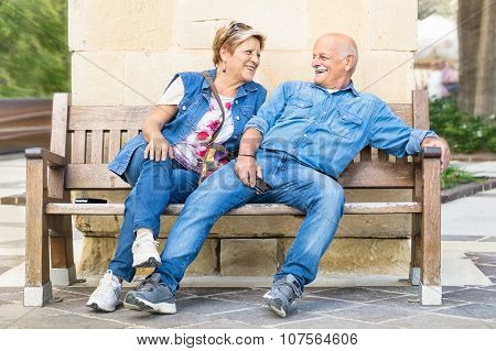 Happy Senior Couple Having Fun On A Bench - Concept Of Active Playful Elderly During Retirement