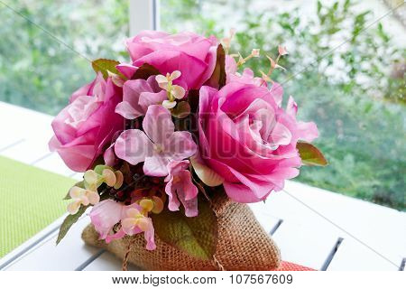 Fake Pink Rose In Sack Bag On White Wooden Table Near Window With Garden View