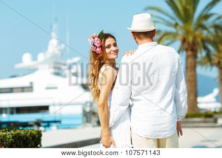 Attractive Young Couple Walking Alongside The Marina With Moored Boats On A Luxury Waterfront In Sum