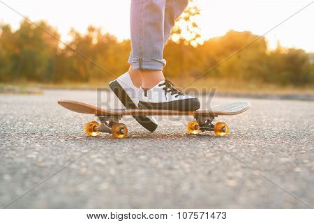 Girl Standing On A Skateboard. Close Up Of Feet And Skateboard.
