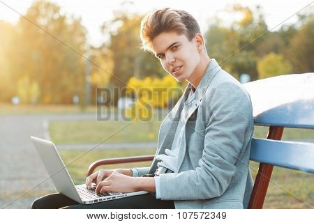 Young Handsome Man Sitting On A Bench In The Park At Sunset. Holds A Notebook In Hands And Working..
