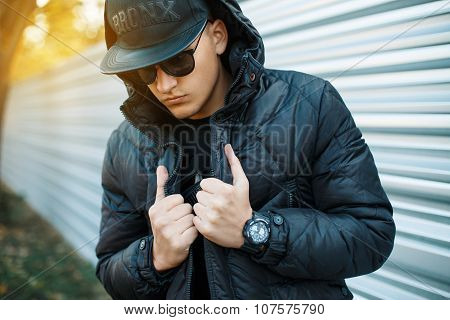 Portrait Of Beautiful Fashionable Guy In A Stylish Black Dress. The Hood On His Head. Beautiful Sunn