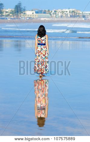 Young girl looking at the ocean and city