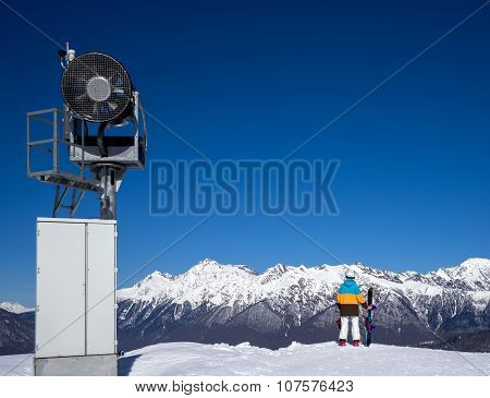 Snow Gun And Snowboarder Woman In Mountains