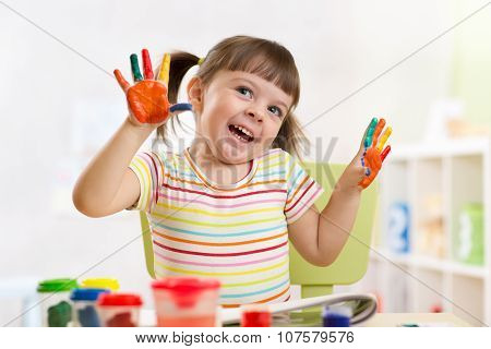 Portrait of kid girl with painted hands