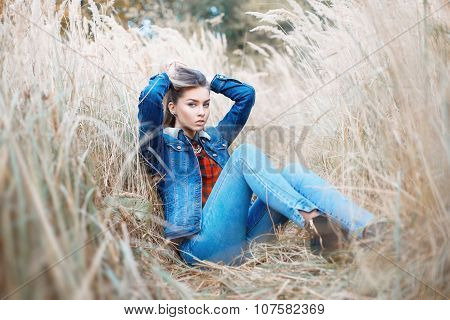 Stylish Fashionable Girl In Jeans Clothes In The Autumn Field.