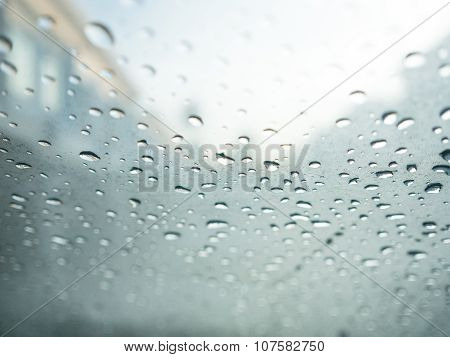 Raindrops On Car's Glass With Blurry Cloudy Sky And Village.