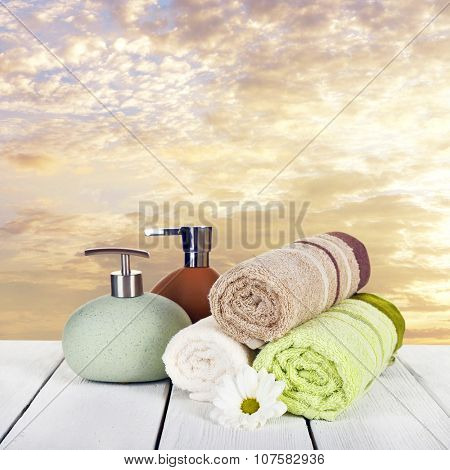 Soft towels with dispenser and flower on sky background