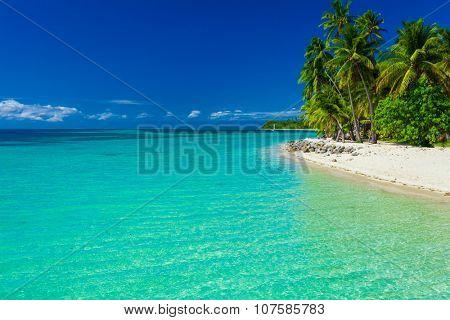 Tropical island in Fiji with sandy beach and clear lagoon