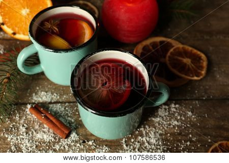 Decorated composition of mulled wine in mugs on wooden table