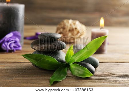 Relax set contains alight wax candles with flowers and pebbles on wooden background, focus on green leaf