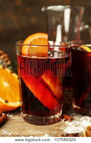 Decorated composition of mulled wine in glasses on wooden table, close up