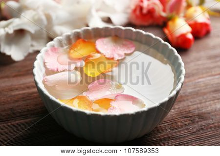 Pink and orange rose petals in a bowl of water on wooden background