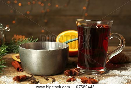 Christmas composition of mulled wine, cinnamon and stew-pan on wooden table