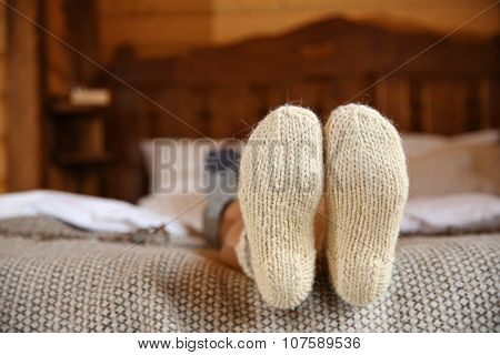 Legs of woman in warm socks on bed