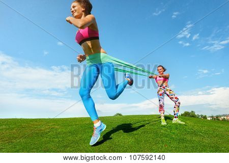 Pilates woman exercising resistance rubber band fitness workout with woman coaches