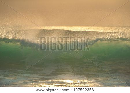 Golden drops of sea wave on sunset
