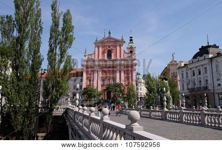 LJUBLJANA, SLOVENIA - JUNE 30: Franciscan Church of the Annunciation and Triple Bridge on the Ljubljanica River in Ljubljana, Slovenia on June 30, 2015