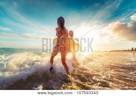 Two ladies running into the sea with surf boards at sunset