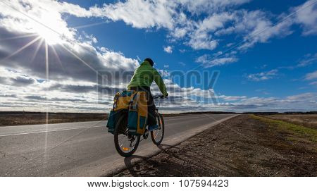 Biker rides loaded bike with a backpack on the road