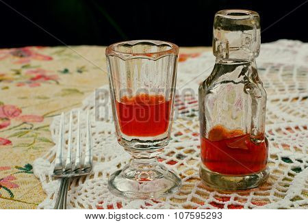 Tiny Bottle Of Liquor And Glass For A Digestif On The Knitted Tablecloth