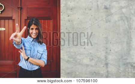 Attractive stylish female is having fun while posing outdoors in urban setting