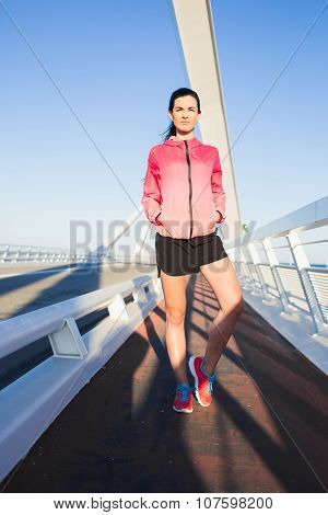 Beautiful healthy fit woman relaxing after evening run in the fresh air in summer
