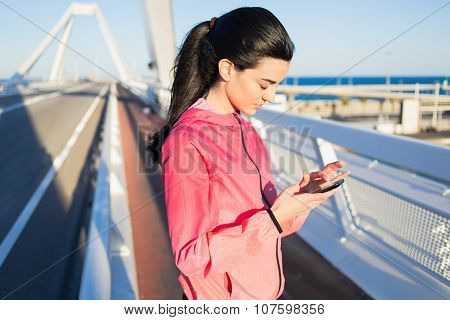 young healthy sporty woman using cell telephone during rest after jog