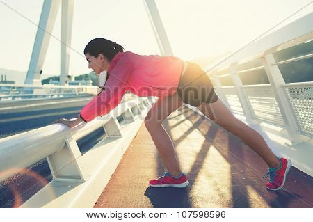 Attractive woman runner dressed in sportswear working out outdoors in evening
