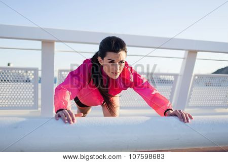 Charming sportive woman in tracksuit doing stretching exercise before her active jog outside