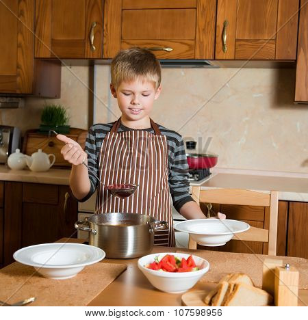 Boy serving Borshch, traditional Russian and Ukrainian soup. Pouring soup into a plate with ladle.
